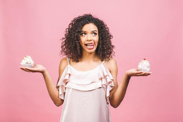 Schwarze amerikanische afrikanische glückliche frau mit lockiger afro-frisur, die ein durcheinander macht, das ein großes ausgefallenes dessert über rosa hintergrund isst. cupcake essen.