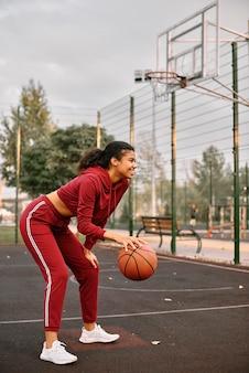 Schwarze amerikanische frau, die basketball auf einem feld spielt