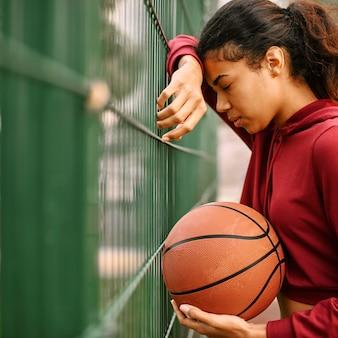 Schwarze amerikanische frau, die basketball mit kopienraum spielt