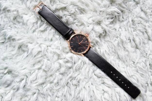 Schwarze armbanduhr auf grauem fell