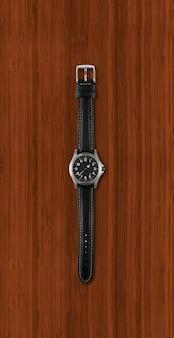 Schwarze armbanduhr lokalisiert auf dunklem hölzernem hintergrund