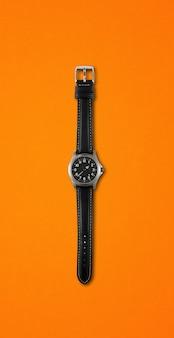 Schwarze armbanduhr lokalisiert auf orange