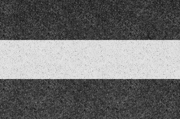 Schwarze asphalthintergrundbeschaffenheit mit gelber linie