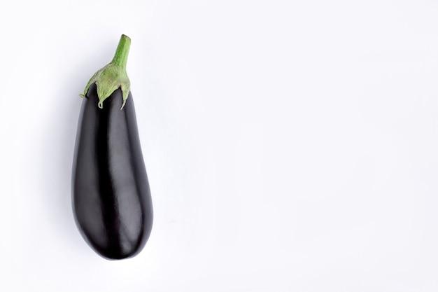Schwarze aubergine auf weißem hintergrund. violette aubergine. minimalismus gemüse