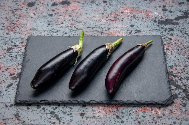 Schwarze auberginen der vorderansicht auf blauem hintergrund des schneidebretts