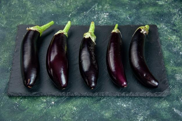 Schwarze auberginen der vorderansicht auf dunklem hintergrund