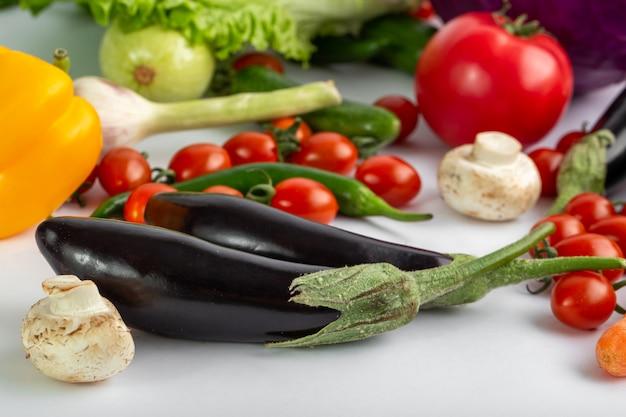 Schwarze auberginen frisches und reifes gemüse wie schwarze auberginen und andere auf weißem schreibtisch