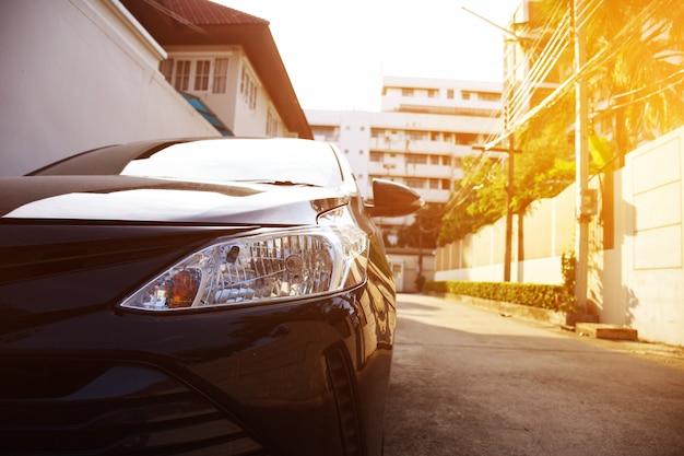 Schwarze autoscheinwerfer auf einer straßenecke mit sonnenlicht erweitert sich