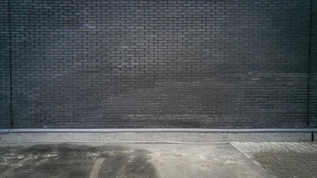 Schwarze backsteinmauer und betonboden
