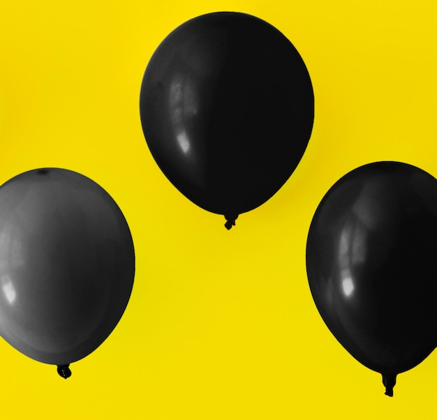 Schwarze ballone auf gelbem hintergrund