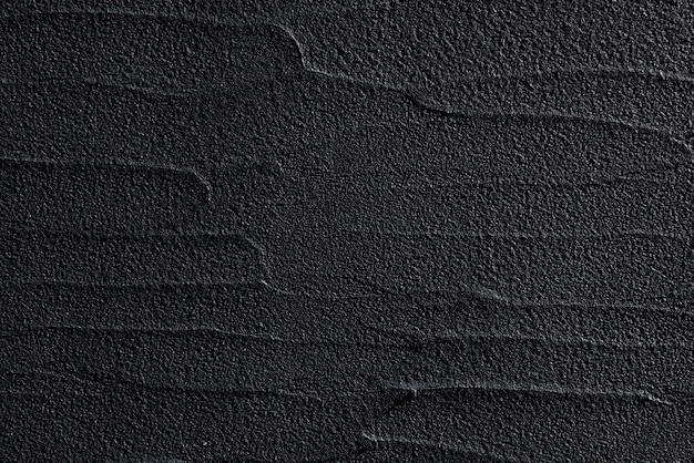 Schwarze betonwand in einem modernen stil mit weichem licht beleuchtet und ihre oberfläche in wellenrelief. elegantes muster.