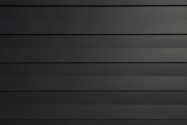 Schwarze betonwand in einem modernen stil mit weichem licht von rechts und abwechselnd hochreliefierter oberfläche.