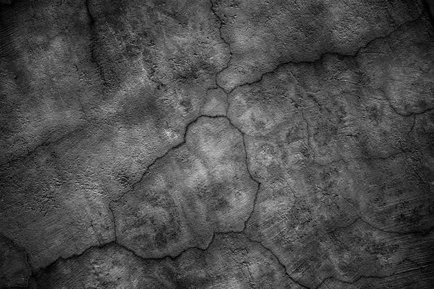 Schwarze betonwand mit rissen bedeckt. düstere oberfläche der zementplatte