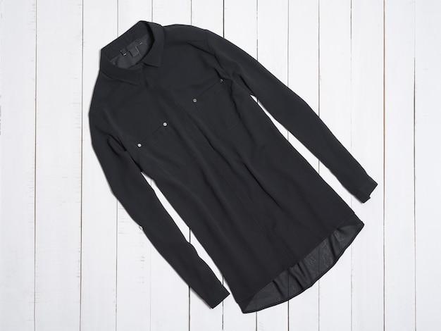 Schwarze bluse auf weißer holzoberfläche. mode-konzept.