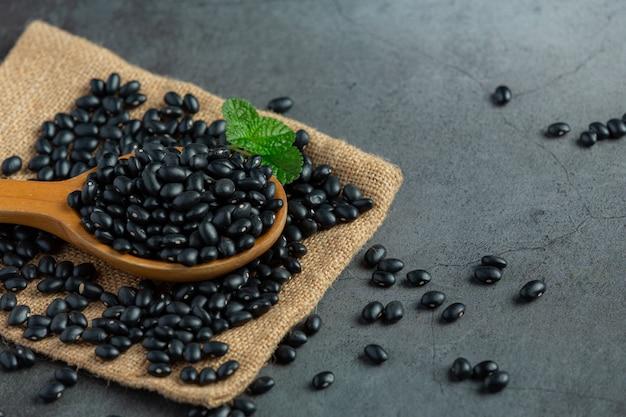 Schwarze bohne in kleinem holzlöffel auf sackstoff legen