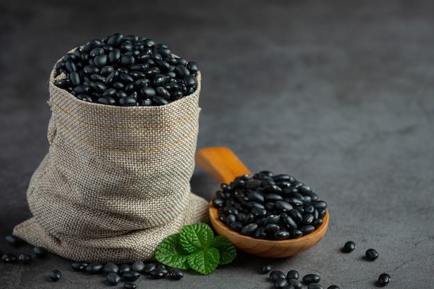 Schwarze bohne in kleinem holzlöffel neben sackbeutel voller schwarzer bohne