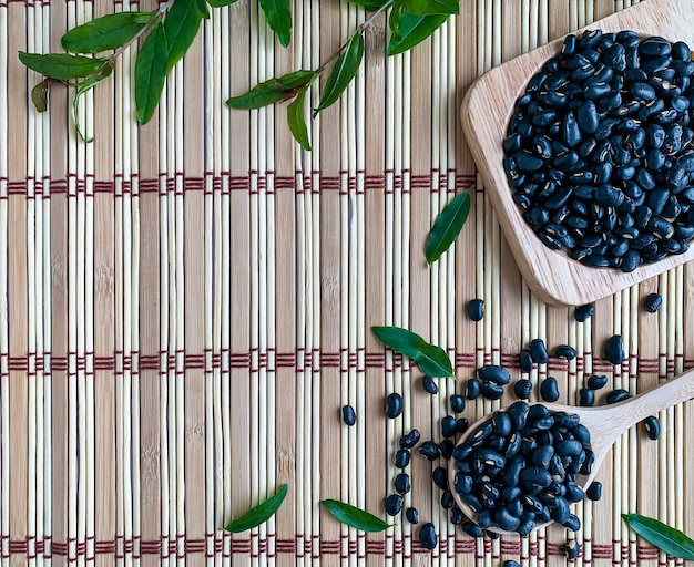 Schwarze bohnen in einem hölzernen löffel auf einer hölzernen matte