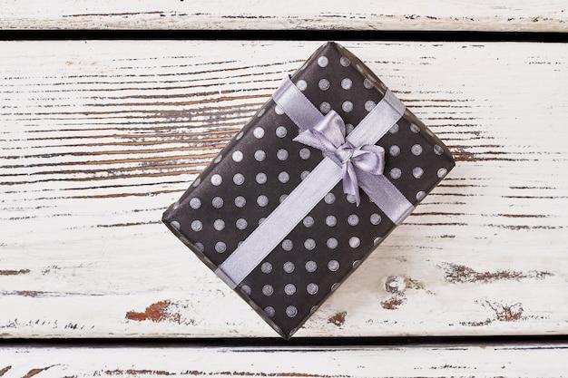 Schwarze box mit violetter schleife. gefleckte geschenkbox und band. wo kann man ein geschenk kaufen.