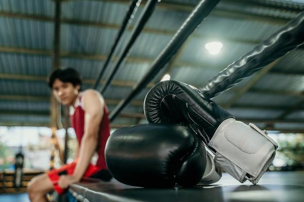 Schwarze boxhandschuhe auf boxring im fitnessstudio. sportgeräte für das training