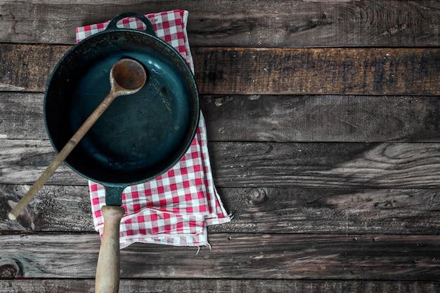 Schwarze bratpfanne mit einem holzlöffel auf einer braunen holzoberfläche