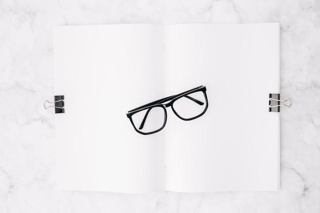 Schwarze brille über dem weißbuch hängt mit zwei bulldoggenclips auf marmorhintergrund