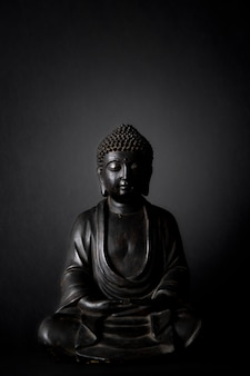 Schwarze buddha-statue mit schwarzem hintergrund