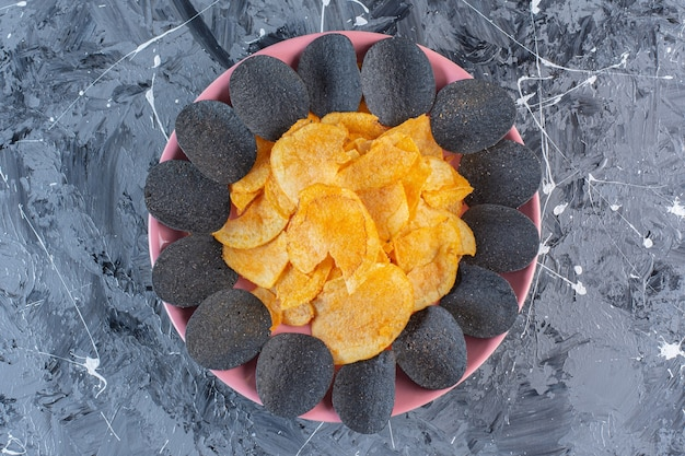 Schwarze chips und kartoffelchips im teller, auf der marmoroberfläche