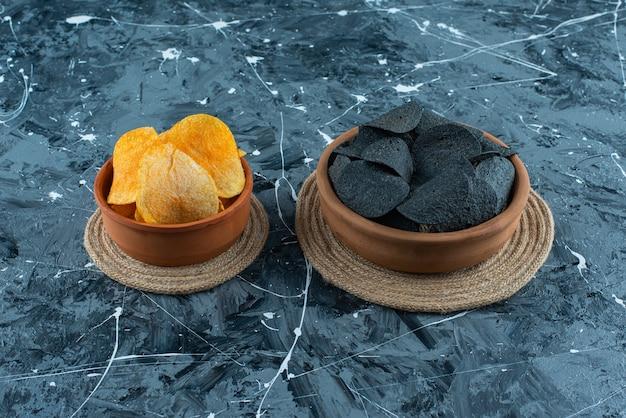 Schwarze chips und kartoffelchips in der schüssel auf untersetzern, auf dem marmorhintergrund.