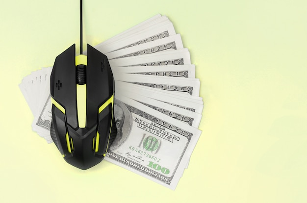 Schwarze computermaus auf vielen hundert dollarscheinen