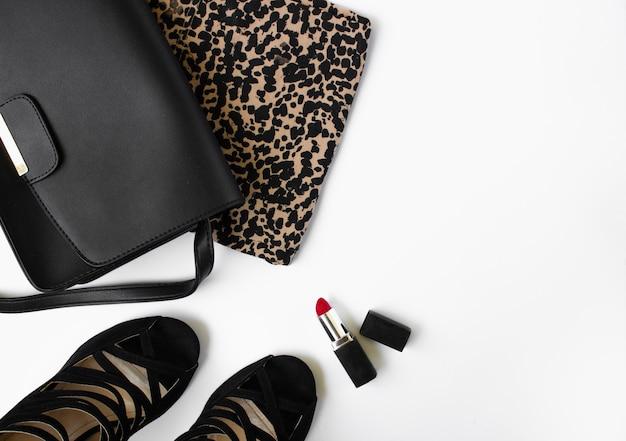 Schwarze damen handtasche schuhe leopard kleidung und roter lippenstift auf einem weißen hintergrund beauty blog konzept