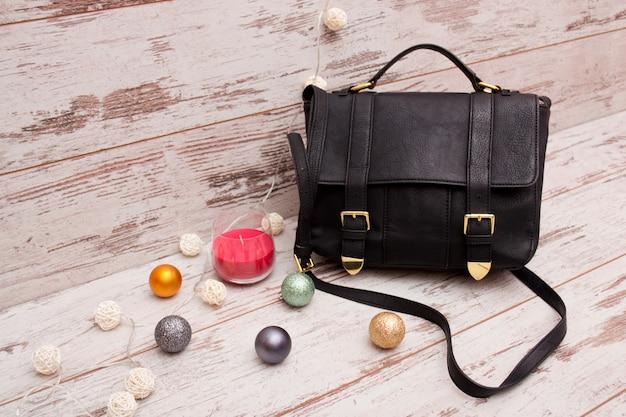 Schwarze damenhandtasche auf einem hölzernen hintergrund, weihnachtsverzierungen, einer girlande und einer kerze