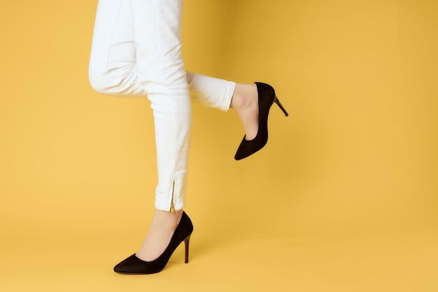 Schwarze damenschuhe beschnittene ansicht gelber hintergrund posiert