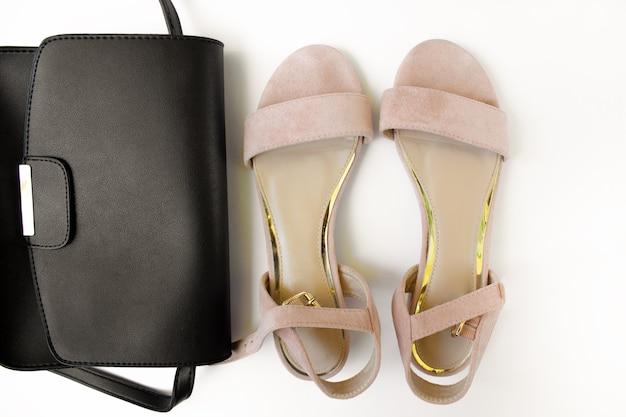 Schwarze damentasche und rosa sandalen auf weißem hintergrund beauty-blog-konzept damenaccessoires