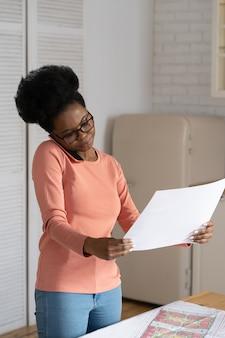 Schwarze designerfrau, die architekturprojekt hält, das auf handyfernarbeit von zu hause aus spricht