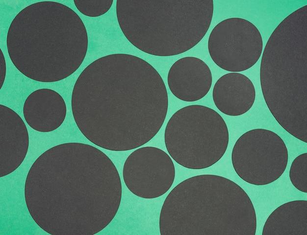 Schwarze designkreisform auf grünem hintergrund