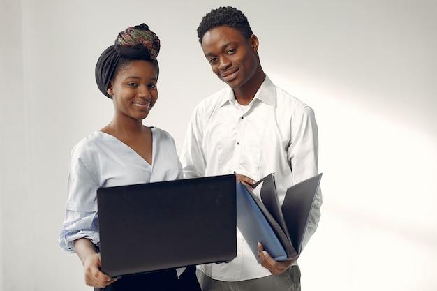Schwarze, die auf einer weißen wand mit einem laptop stehen