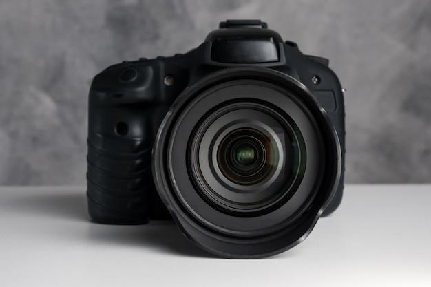 Schwarze digitalkamera auf einem tisch mit schmutzhintergrund.