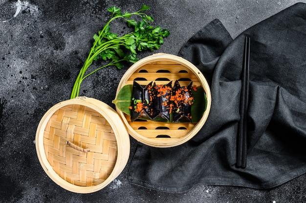 Schwarze dim-sum-knödel im bambusdampfer. asiatische küche. draufsicht
