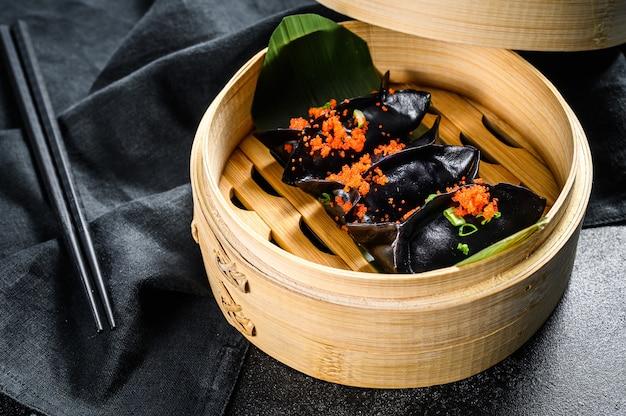Schwarze dim-sum-knödel im bambusdampfer. asiatische küche. schwarzer hintergrund. draufsicht