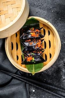 Schwarze dim-sum-knödel im bambusdampfer. asiatische küche