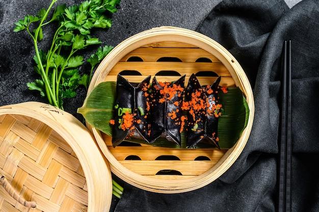 Schwarze dim-sum-knödel in der asiatischen küche des bambusdampfers