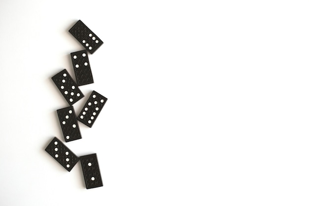 Schwarze dominosteine liegen auf weißem hintergrund, draufsicht. tischspiel. platz für text