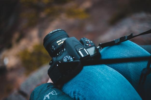 Schwarze dslr-kamera auf person