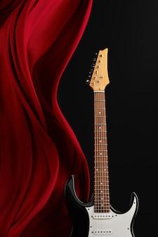 Schwarze e-gitarre, roter vorhang, niemand. streichmusikinstrumentenkonzept, elektroklang, elektronische musik, ausrüstung für bühnenkonzerte
