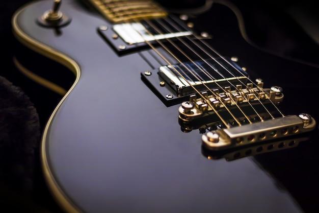Schwarze e-gitarren-nahaufnahme auf dunklem hintergrund