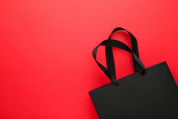 Schwarze einkaufstasche auf einem rot.
