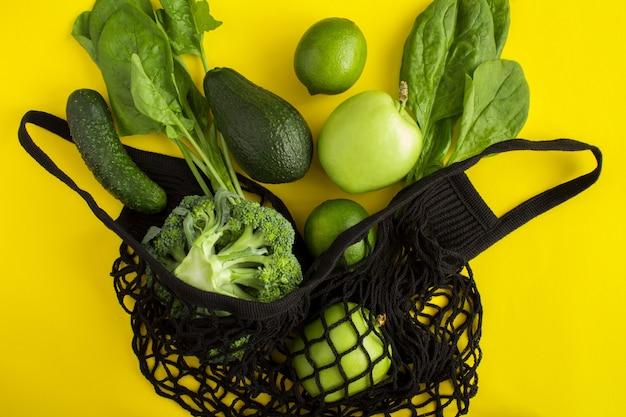 Schwarze einkaufstasche des netzes mit grünem obst und gemüse auf gelb