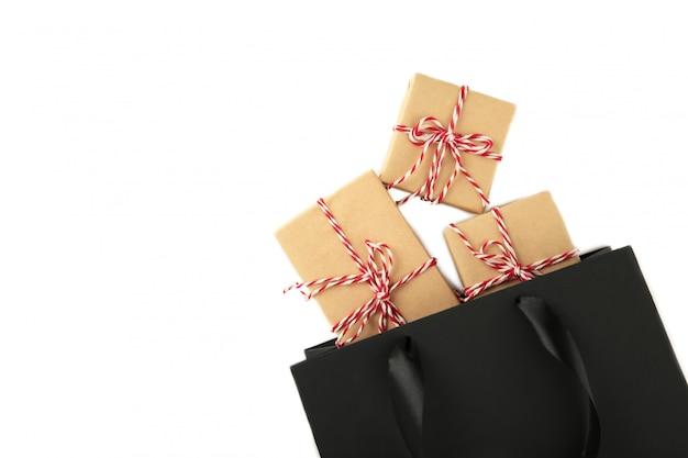 Schwarze einkaufstasche mit den geschenken lokalisiert auf einem weiß.