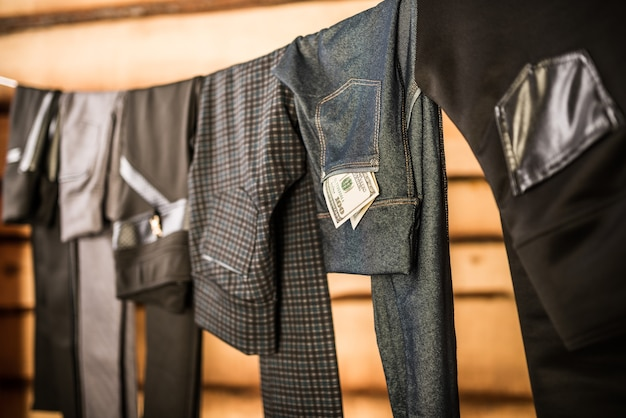 Schwarze, elegante damenhosen und jeans hängen am seil im kleiderschrank.