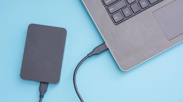 Schwarze externe festplatte, die an einen laptop auf einem blauen hintergrund anschließt.